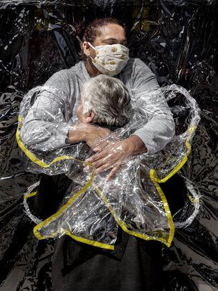 Die Pflegerin trägt beim Foto von Nissen einen Plastikumhang, der Berührungen ohne direkten Körperkontakt möglich macht. Durch die besondere Form des Umhangs erscheint die Pflegerin wie ein Engel.