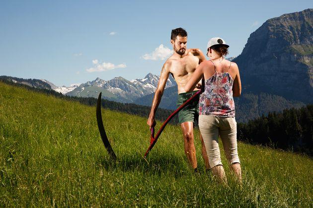 Daniel W. (25) posiert mit Sense vor beeindruckender Bergkulisse.